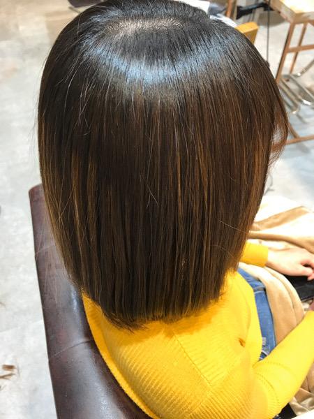 根元に縮毛矯正、中間、毛先に髪質改善トリートメントをしたサイドからみた姿