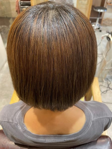 ブリーチ毛に髪質改善縮毛矯正をした髪の写真(後ろ姿)